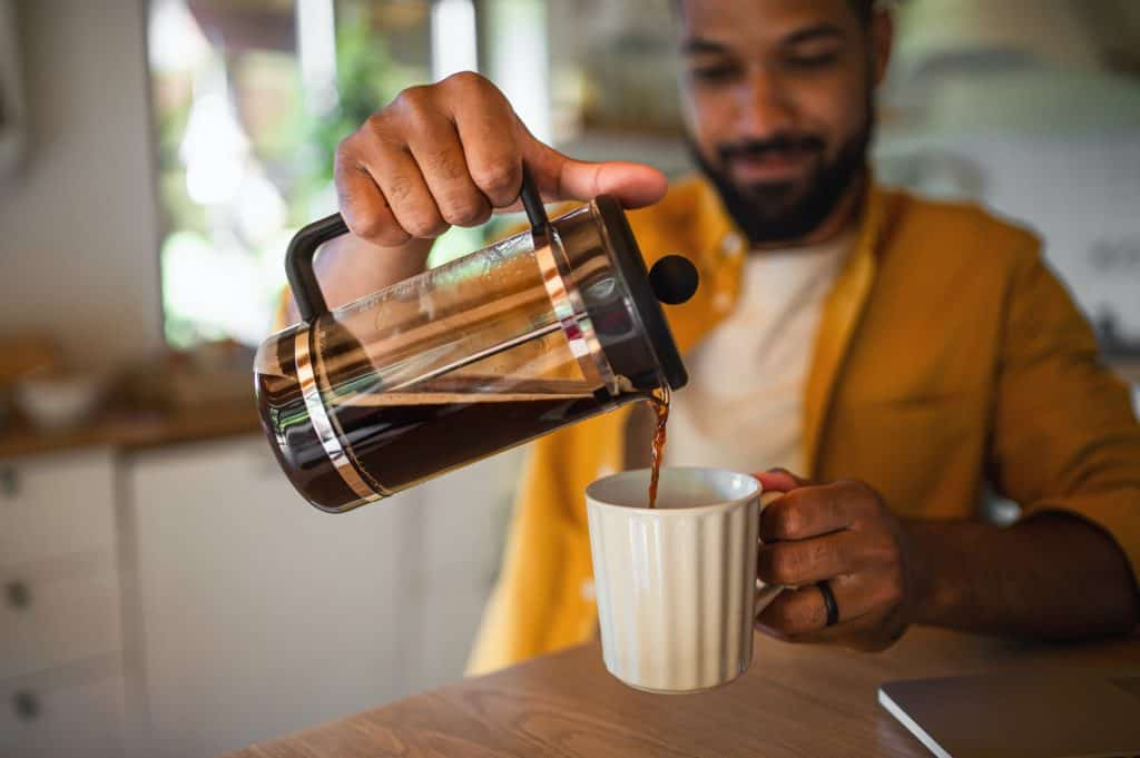 Young man pouring coffee from french press working indoors, home office concept